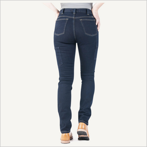 Backside view of woman wearing Dovetail Maven Slim Work Pant in Indigo Power Stretch Denim. She is wearing a grey shirt and camel work boots and is visible from the waist down. Her hands are on her hips.