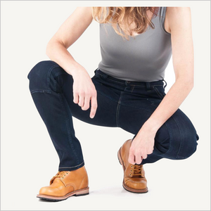 Woman squatting down, wearing Dovetail Maven Slim Work Pants in Indigo Power Stretch Denim. She is also wearing a grey tank top and camel work boots.