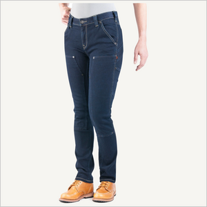 Woman wearing Dovetail Maven Slim Work Pants in Indigo Power Stretch Denim. She is visible from the waist down.  She is wearing a white shirt and camel work boots and her right hand is on her hip, left hand is hanging at her side.