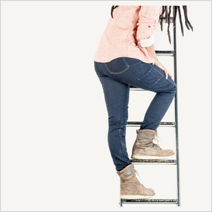 Lifestyle image of a woman wearing Dovetail Maven Slim Work Pants in Indigo Power Stretch Denim. She has on a pink work shirt and light brown work boots. She is claiming up a black ladder and her back is facing the camera. Her body is visible from her upper back down to her shoes.