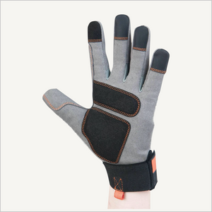 One hand raised in the air, wearing Dovetail Multi-Purpose Work Glove. The glove is grey on the palm side, with black and grey tips and a black and orange cuff. The palm side  is facing the camera and the fingers are spread out.