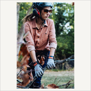 Lifestyle image of a woman wearing Dovetail Multi-Purpose Work Gloves. She is working outside and holding onto a tree branch. She is wearing a red work shirt and denim pants. She is also wearing a helmet and ear protection and sunglasses. She is facing the camera.