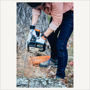 Lifestyle image of a woman wearing Dovetail Multi-Purpose Work Gloves. She is bending at the waist and holding a chainsaw. She is outside and cutting a log. She is also wearing a red work shirt and denim pants.