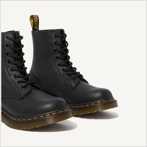 Side angled view of a pair of Dr. Martens 8 Eye 1460 Slip Resistant Lace Boots in Black.