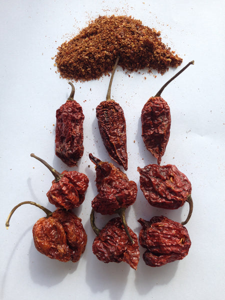 A pile of the three chilli powder with Carolina Reapers, Trinidad Scorpions and Naga Ghost Chillies underneath