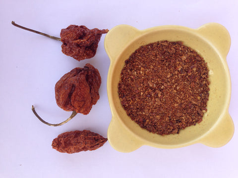 A bowl of our powerful three chilli powder with the three chillies beside it. Carolina Reaper, Trinidad Scorpion and Naga Ghost chillies.
