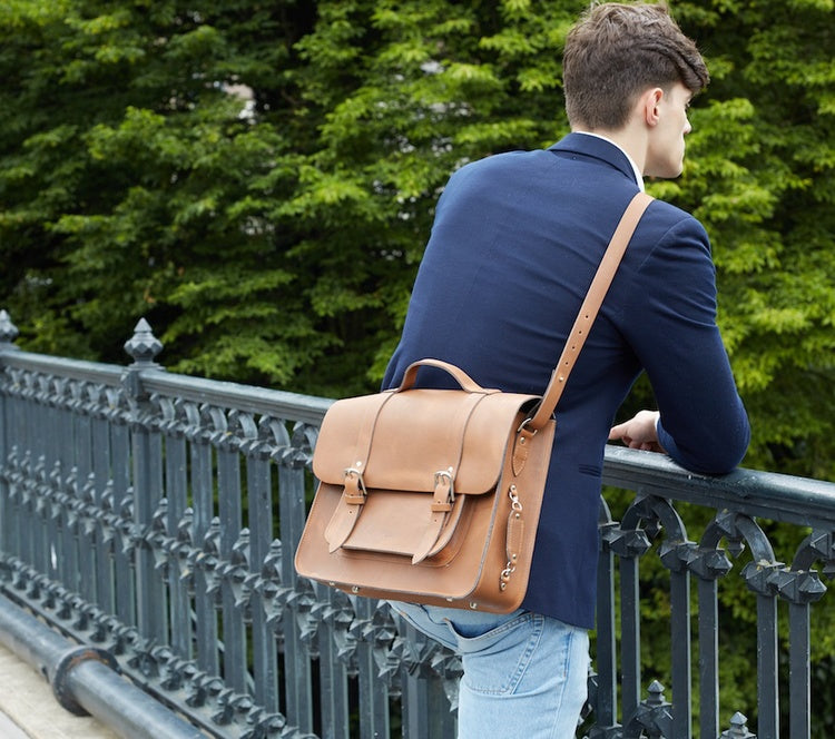 Tan leather satchel bike bag carried by a male model