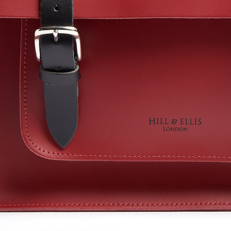 Red leather satchel cycle bag detail of Hill & Ellis logo embossing
