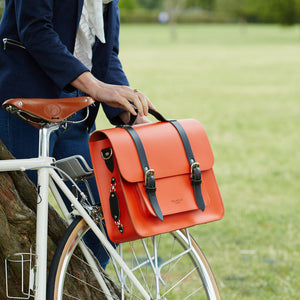 Orange leather satchel cycle bag attached to bicycle