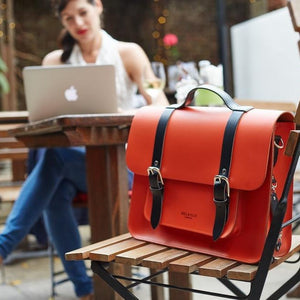 Orange leather satchel cycle bag in cafe