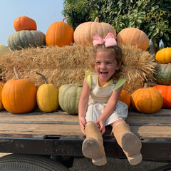 owner's daughter in a pumpkin patch
