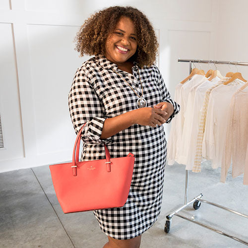 Fashionable woman wearing a plaid Spring dress, holding a red Kate Spade handbag.