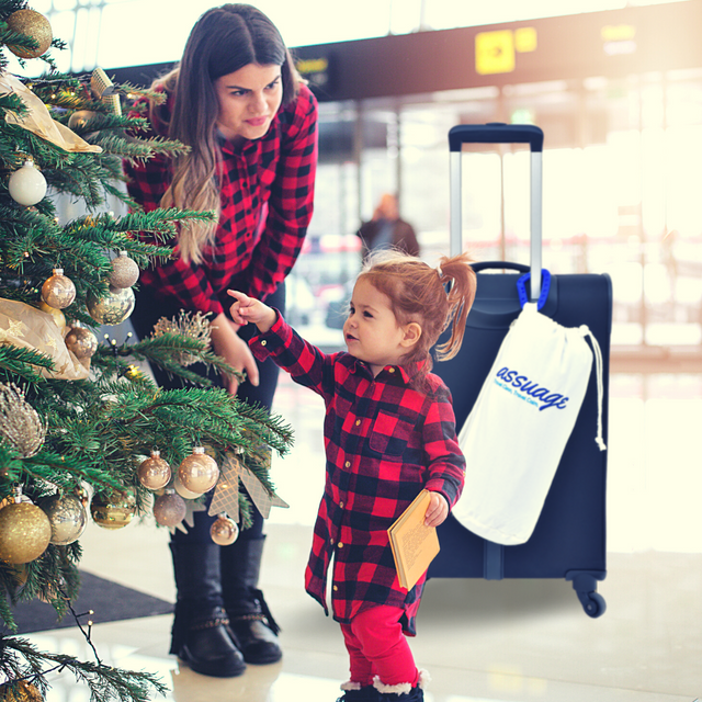 Mom and daughter at an airport with their Assuage Ultra Cozy seat protector clipped to their carry-on luggage as they travel home for the holidays.