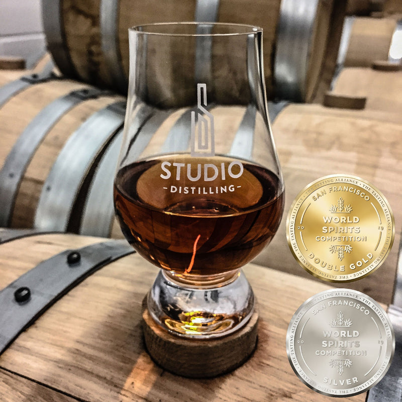 Sample glass of Studio Distilling Bourbon on a barrel with medals