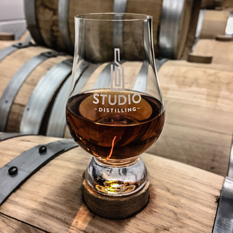 Sample galss of Studio Distilling Bourbon on a barrel
