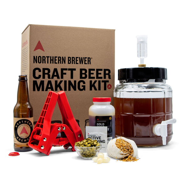 Fermentor with airlock, bottle capper, bottle, extract in a container, a bowl with hops, and a mesh bag with specialty grains