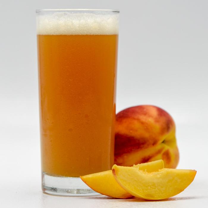 Funktional Fruit Peach Sour homebrew in a glass beside a whole and a sliced peach