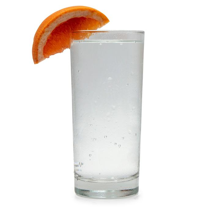 Ruby Grapefruit Hard Seltzer in a glass with a grapefruit wedge