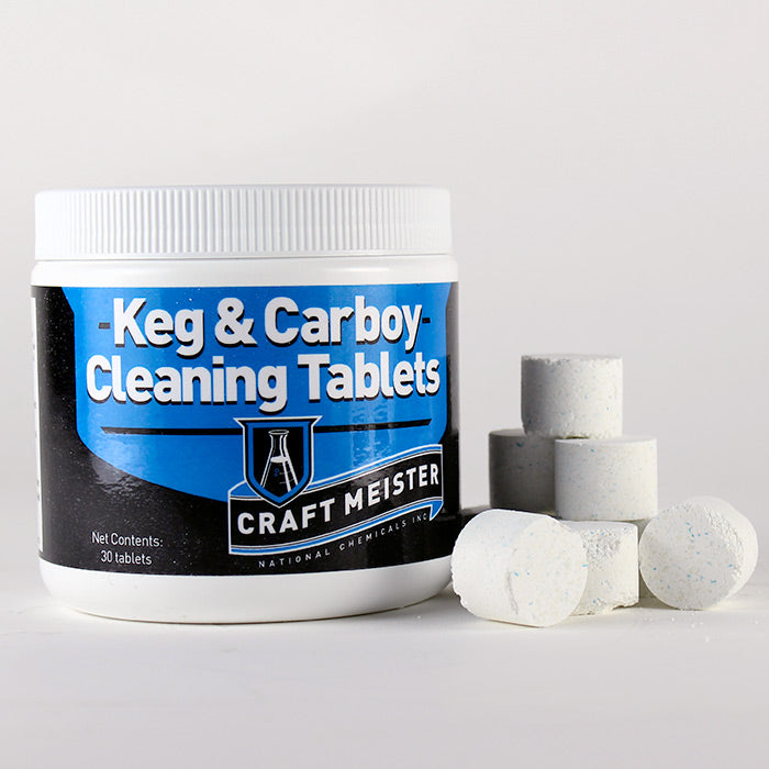 Keg and carboy cleaning tablets in a pile beside its container