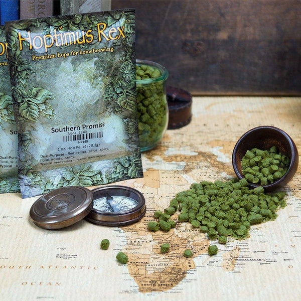 Southern Promise Hop Pellets spilling out of a display bowl onto a map of Africa beside its packaging and a compass