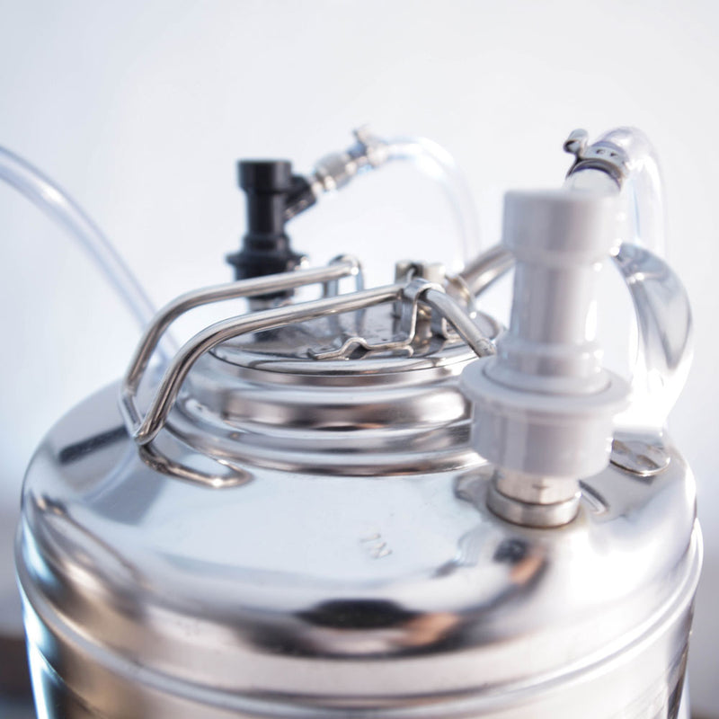 A corny ball lock keg attached to a gas regulator and a beverage line