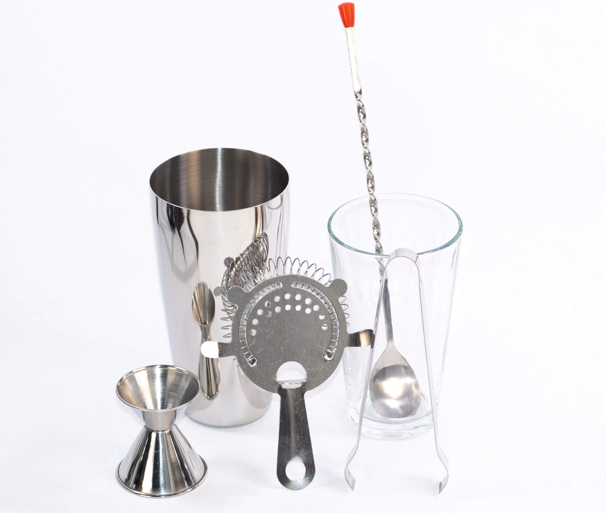 Minimalist cocktail kit featuring strainer, cocktail spoon, jigger, shaker, and ice tongs including everything you need to make all your favorite cocktails at home