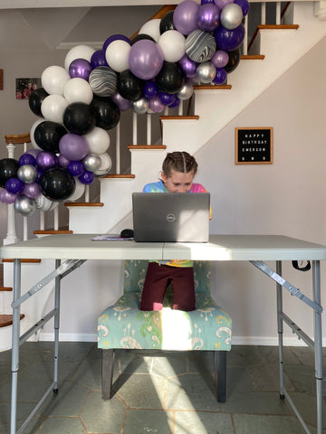 little girl looking at laptop with balloons behind her