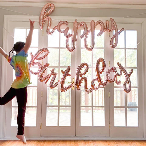 little girl jumping in front of happy birthday balloon sign and french door windows