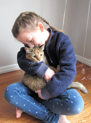 little girl in blue jacket and jeans hugging a gray kitten