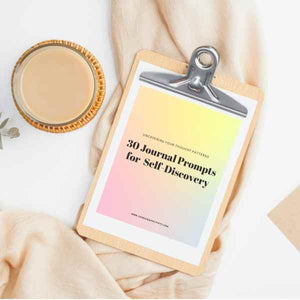 A photo of printed Choosing Positivity Journal Prompts on a clipboard with a candle and cozy blanket