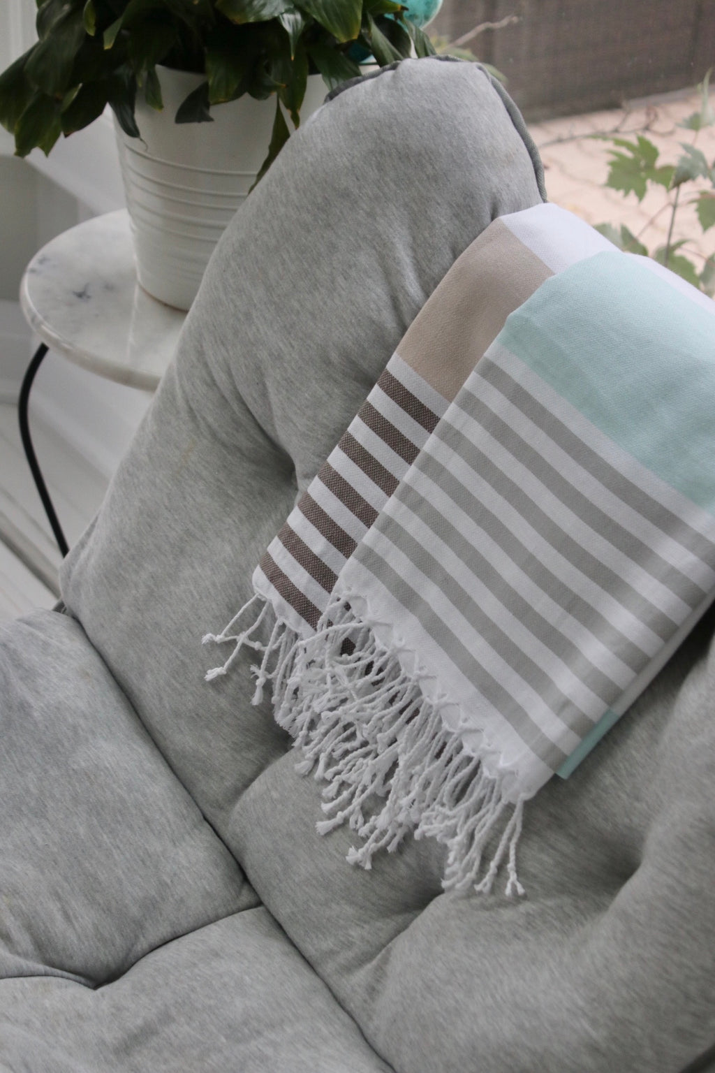 koton kulture toronto turkish towel the classic peshtemal with white stripe at the very bottom and tassels in turquoise or in beige by a plant on a chair
