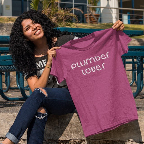 Beautiful woman smiling as she holds up her new PLUMBER LOVER t-shirt