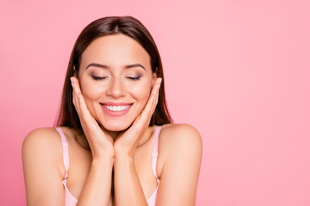 Girl with head in hands smiling against pink background