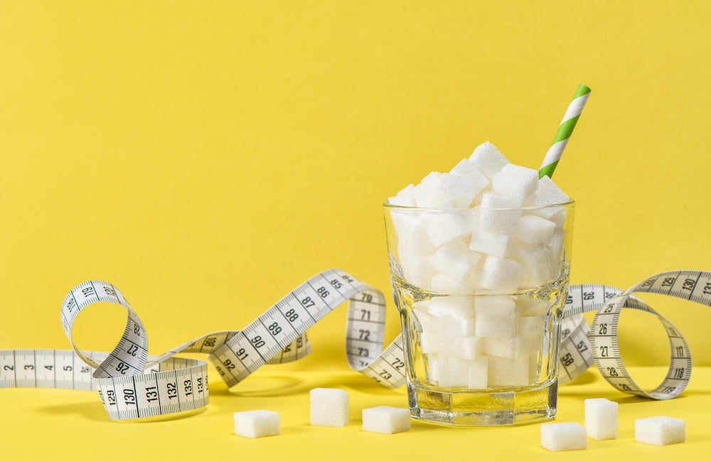 Glass of sugar cubes with measuring tape