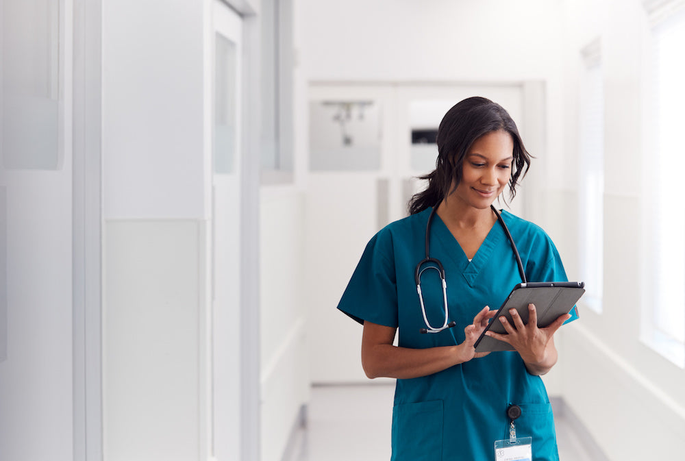 woman in scrubs with clipboard