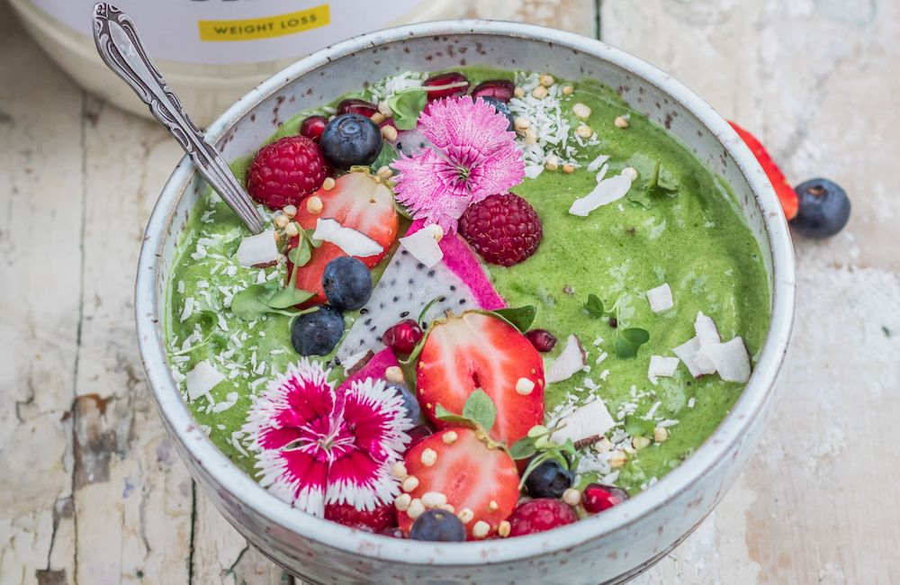 Green spinach smoothie bowl with strawberries and raspberries