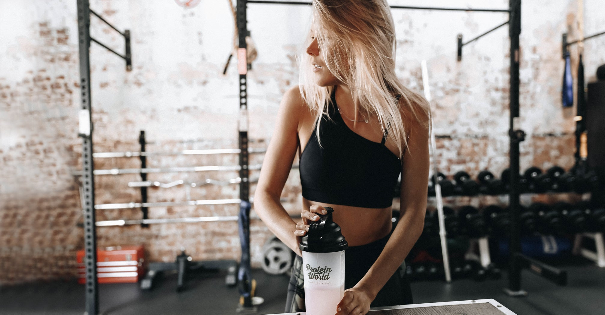 Girl with Protein World shaker in the gym