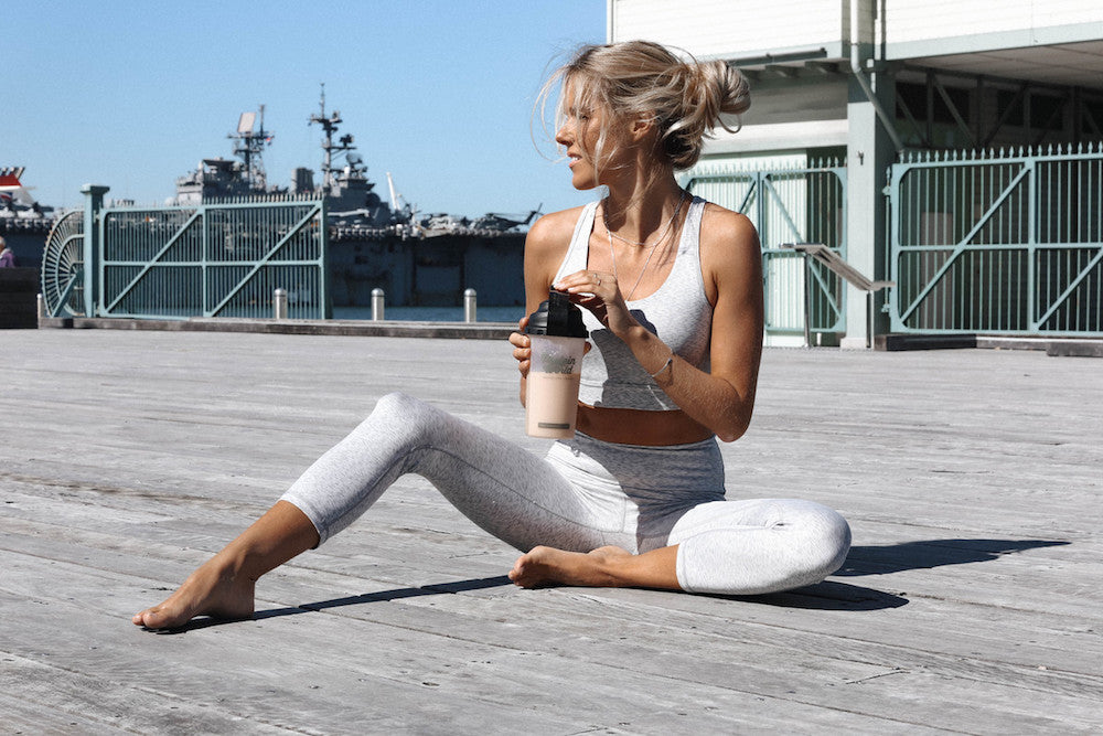 Woman sat down holding Protein World shake in workout clothes