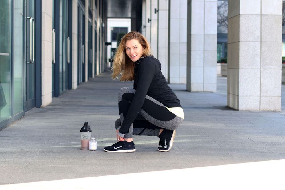 Women bent down tying her shoelace in workout clothes with Protein World shake next to her