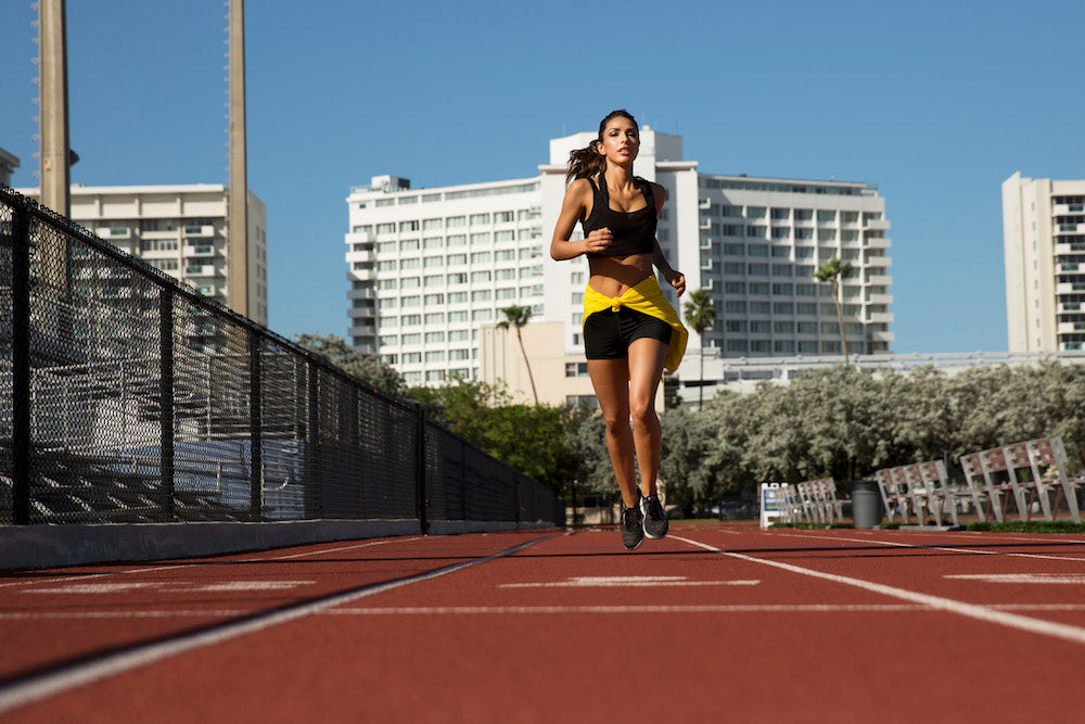 woman running on track from a distance