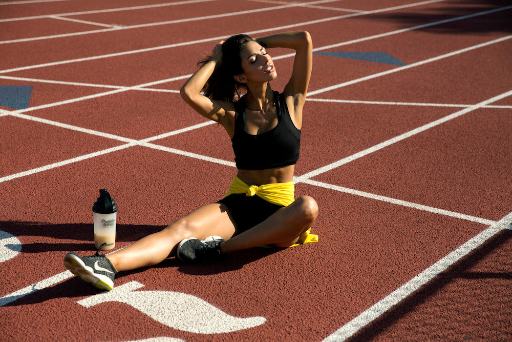 woman sat. on the ground at a track