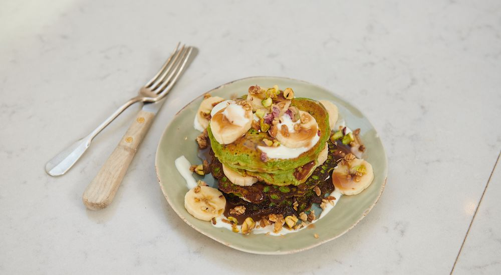 Green spinach pancakes with banana and honey on top