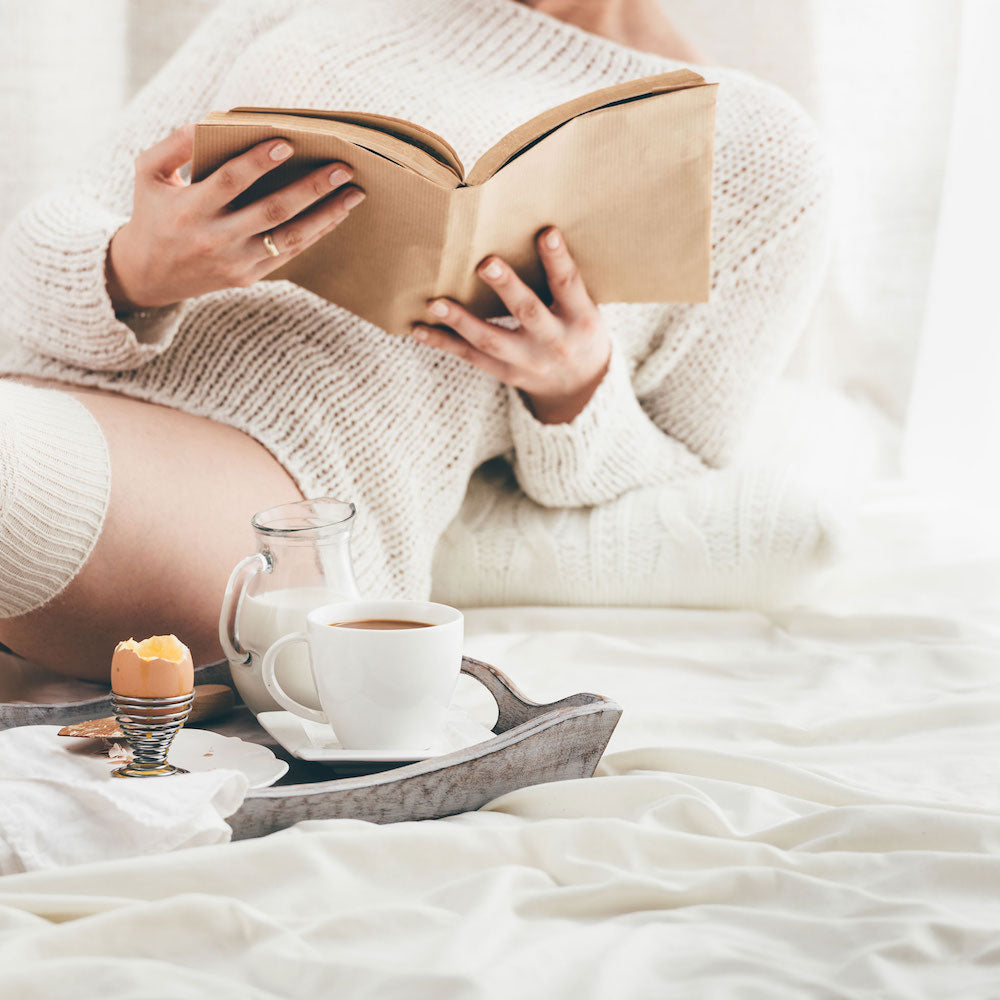 girl on bed with egg breakfast