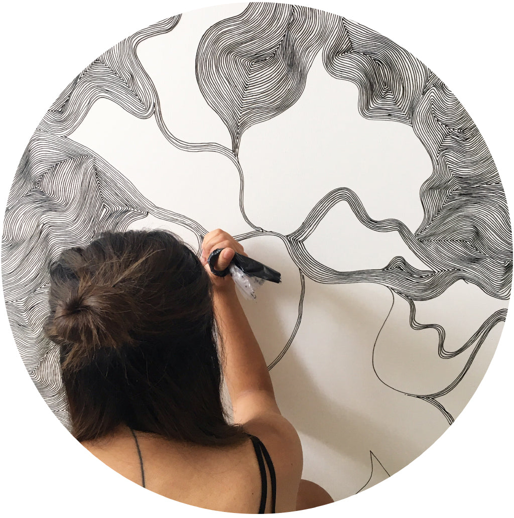 Linegirl artist drawing on her wall