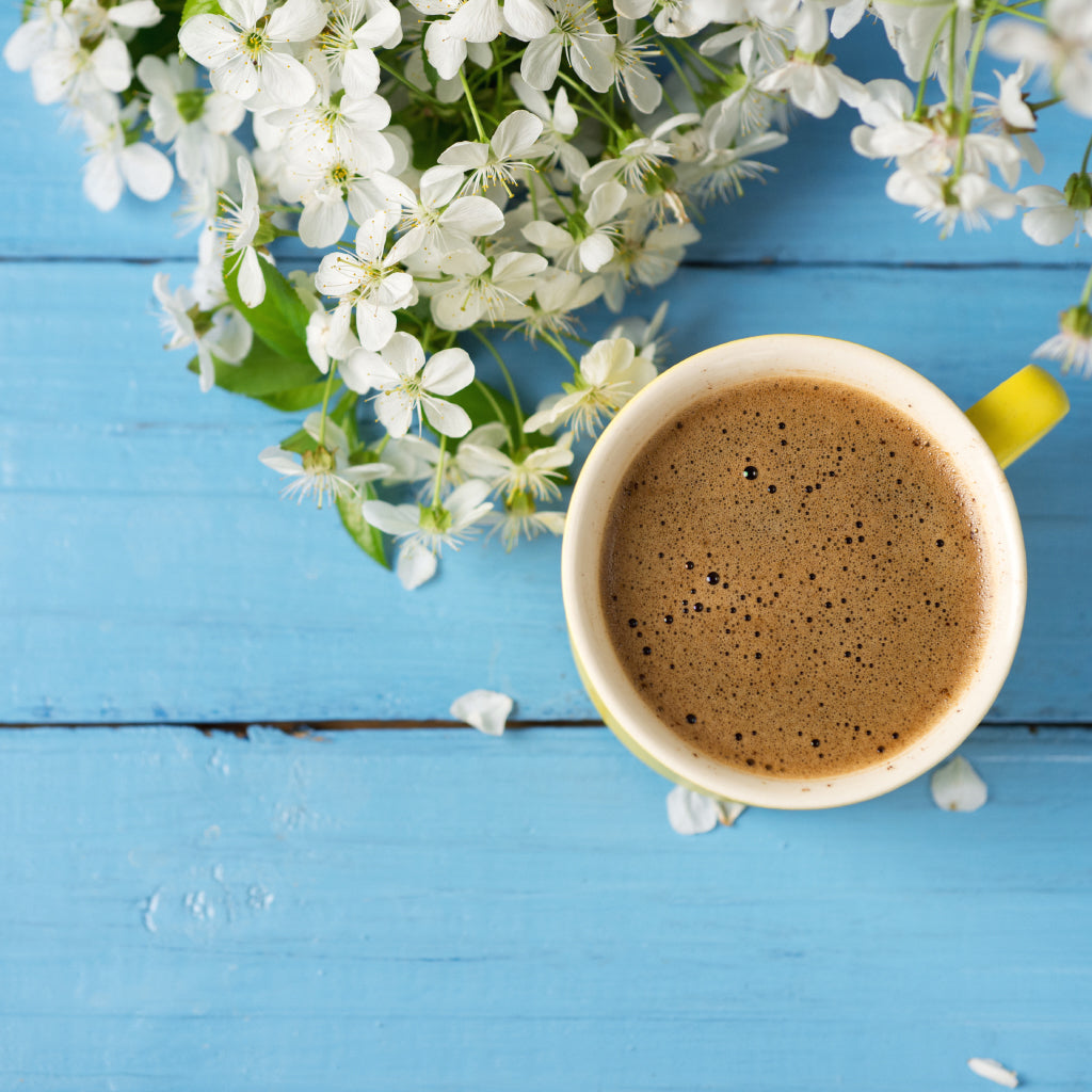 cup of coffee on a blue picnic table with jasmine flowers - shot from above