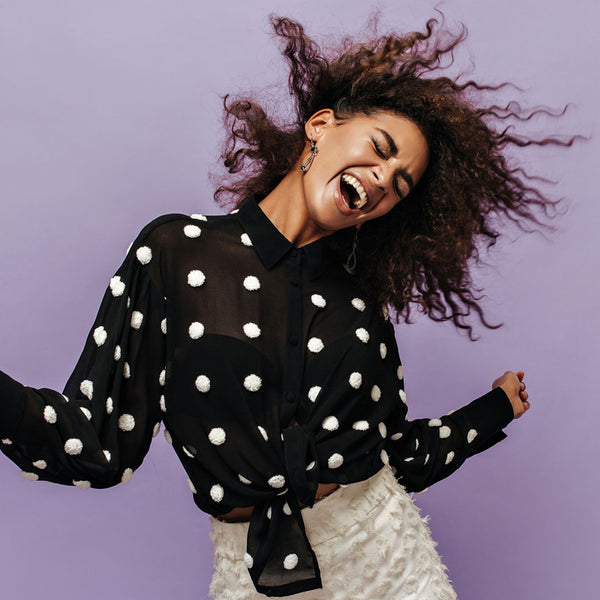 Happy fashionable woman wearing a black top with white polka dots and white pants.