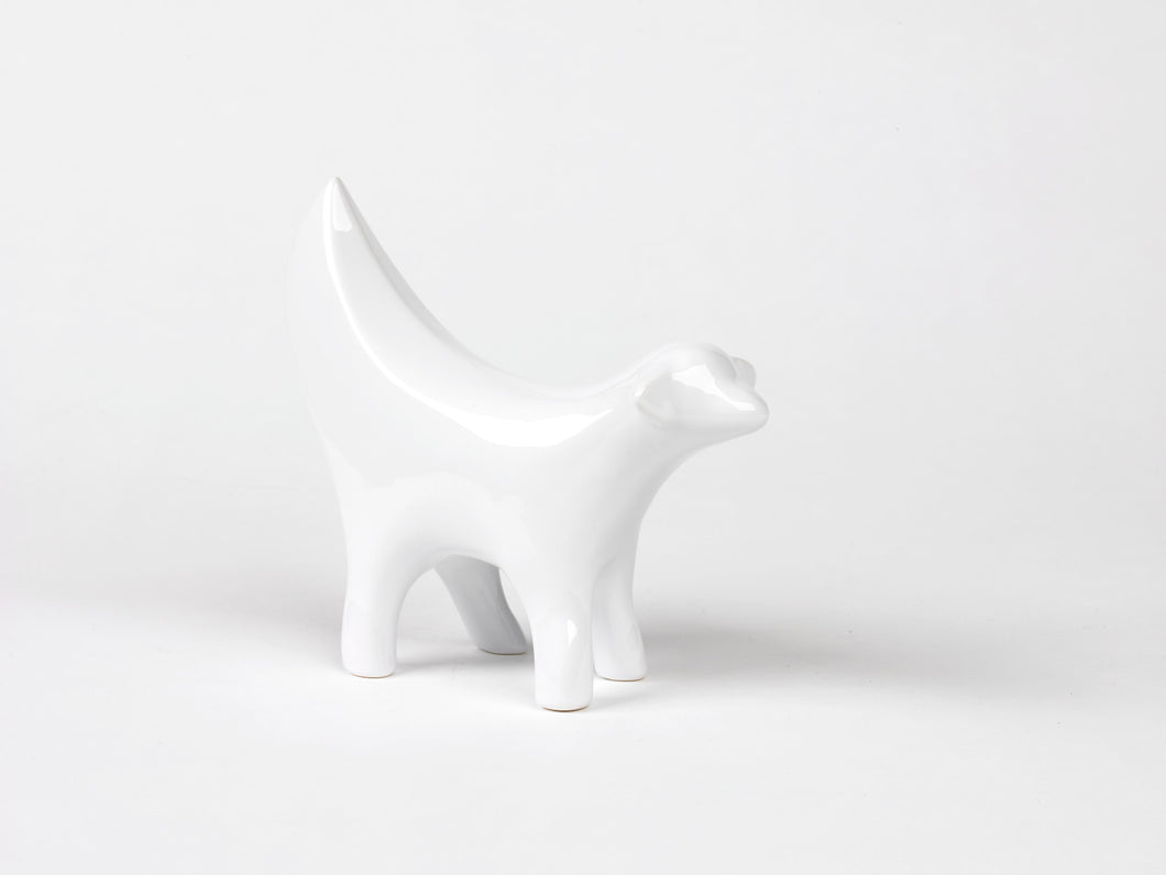 Ceramic white statue, shaped as the front half of a lamb combined with a banana.
