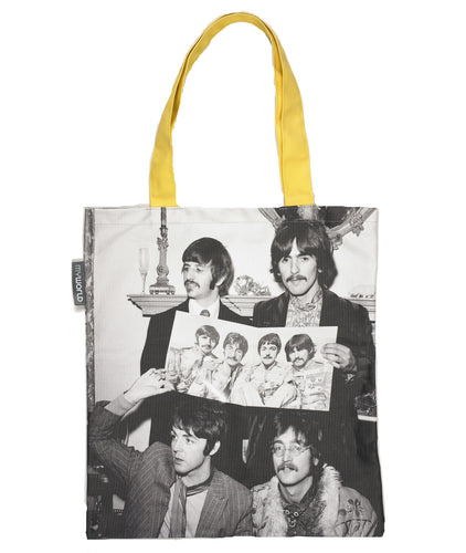 Long handled tote bag with yellow handles and the body of the bag printed with a photo of the beatles holding up a promotional photo of themselves.