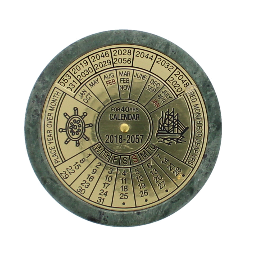 Front view of a brass circular 40 year calendar, with rotating disks to show the dates.