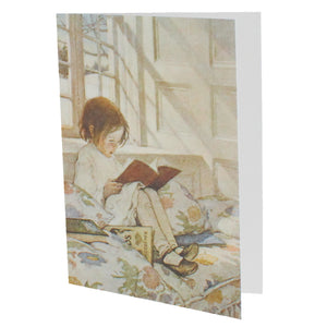 Greeting card showing a painting of a small girl, sat in a bay window reading a book.